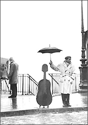 Cellist protects his cello with an umbrella
